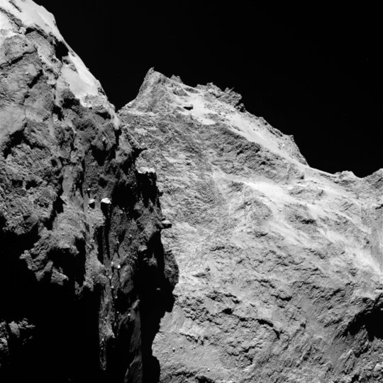 "Jagged cliffs and prominent boulders: In this image, several of 67P's very different surface structures become visible. The left part of the images shows the comet's ""back"", while the right is the back of its ""head"". The image was taken by OSIRIS, Rosetta's scientific imaging system, on September 5th, 2014 from a distance of 62 kilometers. One pixel corresponds to 1.1 meters. <br /><br />"
